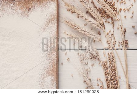 Baking class or recipe concept on white background, sprinkled wheat flour, grain and ears with free copy space. Top view on wooden board on table. Cooking dough or pastry.