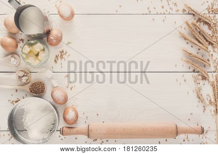 Baking background. Cooking ingredients for yeast dough and pastry, eggs, flour and milk on white rustic wood. Top view with copy space, mockup for menu, recipe or culinary classes.