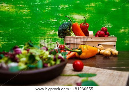 Sweet pepper, brocoli and cherry tomato. Potatoes and red radish. Natural raw vegetables. Organic bio food on rustic wooden table.