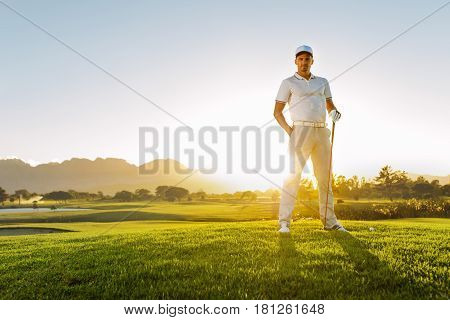 Full length of young male golfer standing on golf course on a summer day. Portrait of young man with golf sticks on field.