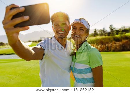 Smiling Young Couple Taking Selfie At Golf Course