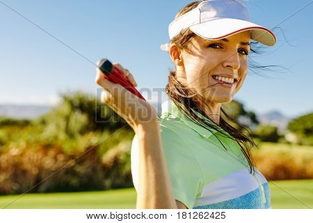 Close up portrait of happy female golfer holding golf club on field. Beautiful young woman standing on golf course and smiling.