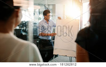 Businessman explaining pie chart to colleagues in office. Mature executive giving presentation to coworkers in modern office.