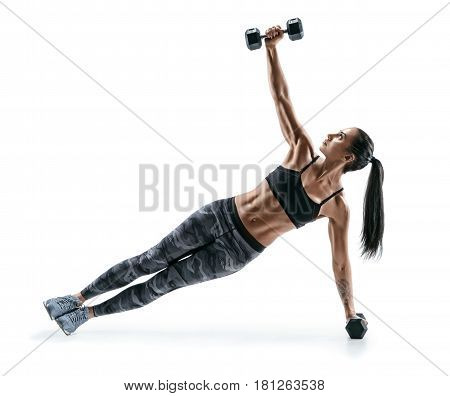 Beautiful strong woman doing fitness plank position exercises with dumbbells. Photo of woman in silhouette on white background. Fitness and healthy lifestyle concept