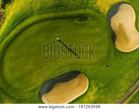 Aerial view of players on a green golf course. Golfer playing on putting green on a summer day.