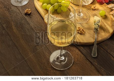 A photo of a wine and cheese tasting, with bread, grapes, and glasses of wine, with a place for text