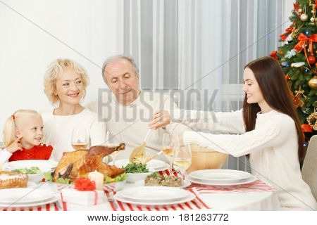 Happy family having Christmas dinner in living room
