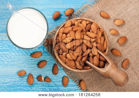 Almond milk in a glass and almonds in a bowl on blue wooden background. Top view.