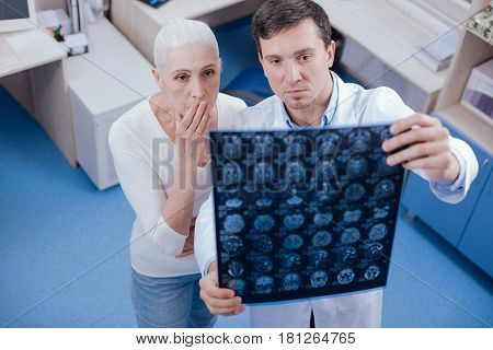 Bad diagnosis. Serious shocked unhappy woman looking at her brain X ray images and covering her mouth while being astounded with her diagnosis