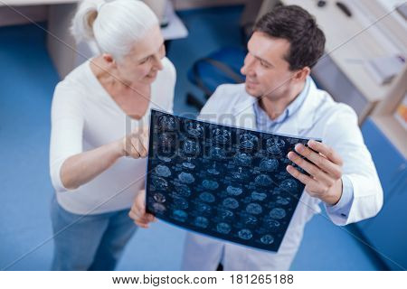 MRI scan. Selective focus of brain images being held by a joyful delighted cheerful doctor while interacting with his patient
