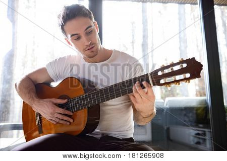 Young man trying to produce new melody with guitar while sitting in living room