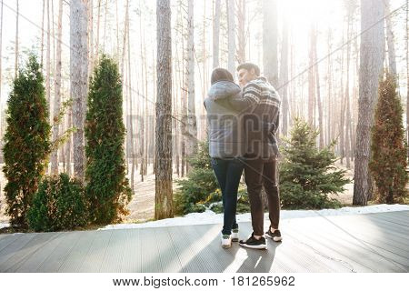 Back view of hugging young man and woman standing on doorstep of house