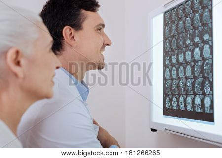Notable improvements. Joyful smiling male doctor standing in front of the X ray brain images and smiling while being happy for his patient