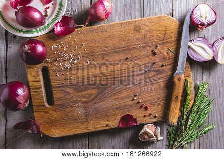 Red Onion Bulb On Brown Cutting Board.