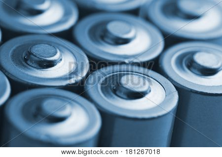 low angle blue close up of electric batteries and accumulators AAA AA with selective focus on top