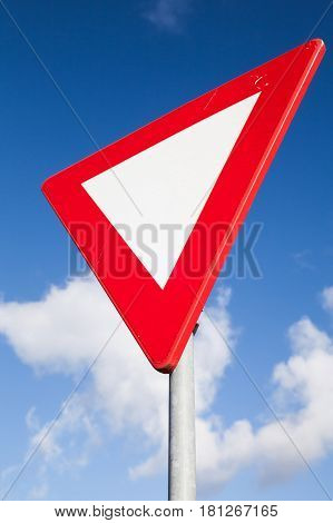 Give Way Road Sign Over Blur Cloudy Sky