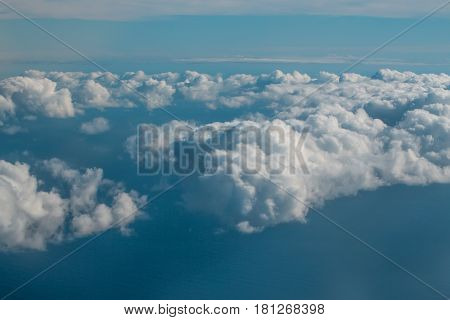 Thick fluffy white clouds on blue sky celestial dome over idyllic sea or ocean water surface background. Overcast view from plane flight