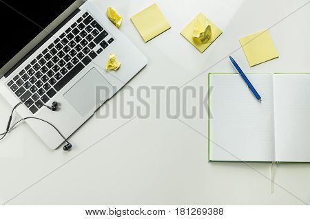 Top view of minimalistic home office work place with laptop and note pad. White desk with note book, portable computer, earphones and yellow sticky notes flat lay