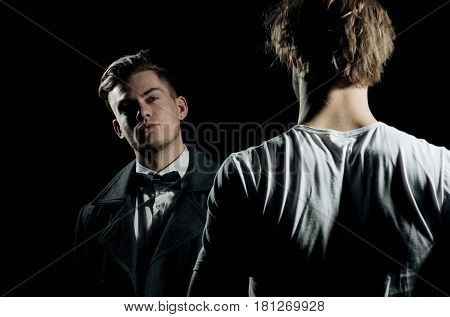 Two handsome men standing opposite on black background. businessman in classic bow tie shirt and dark coat. Male model in white tshirt casual wear. Fashion confrontation