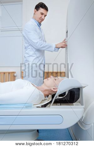 Medical examination. Nice calm elderly woman lying on an examination table and closing her eyes while being examined in the lab