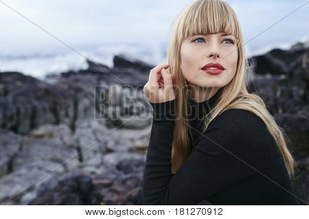 Bewitching blond woman in black dress looking away
