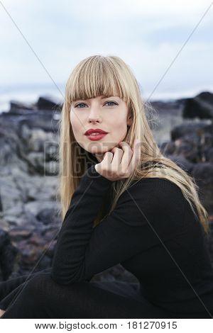 Beauteous blond woman in black dress portrait