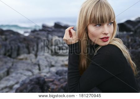 Bewitching young woman in black dress looking away