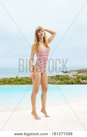 Sensuous young woman in swimsuit at poolside