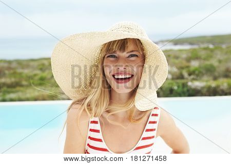 Laughing young lady in sunhat and swimsuit portrait