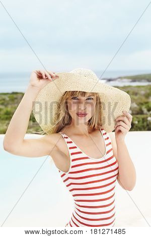 Posing young woman in sunhat and swimsuit portrait