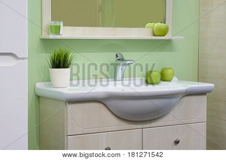 White inset ceramic washbasin with glossy metal mixer in green bathroom