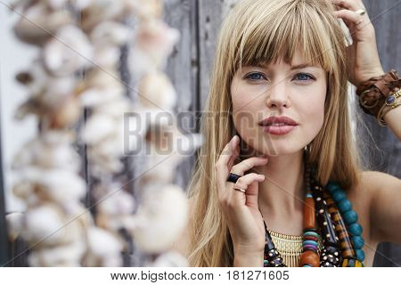 Beautiful young blond woman wearing boho necklace portrait