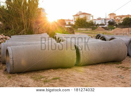 Industrial concrete drainage pipes stacked for construction. New tubes.