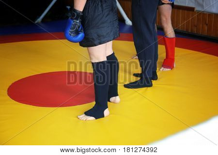 Referee and kickboxing fighters in a ring after competition