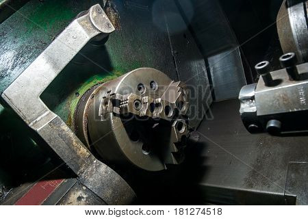 Old rotary lathe machine tool equipment in factory interior not in work