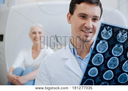 My patient is getting better. Happy positive male doctor holding CT scan results and smiling while looking at them