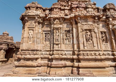 Walls with Indian design of stone relief on 7th century temples in Pattadakal of Karnataka, India. UNESCO World Heritage site with stone carved temples.