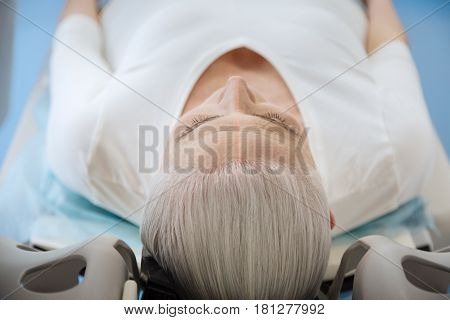 MRI scanner. Nice grey haired elderly woman lying on the examination table and undergoing medical examination while having health problems