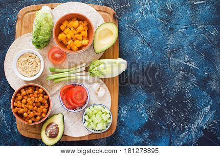 Vegetarian tortillas with ingredients on the wooden board chickpeas butternut squash spring onion cucumber avocado on the dark blue table top view copy space for text