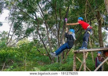 Labuan,Malaysia-Feb 11,2017:Happy muslim girl playing the flying fox in Labuan,Malaysia.There will be more zipline in Malaysia,especially when there have so much natural resources & rainforest.