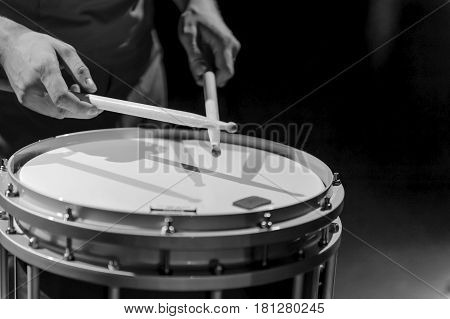 The hands of a drummer with a marching drum. Black and white photo of the hands of a musician