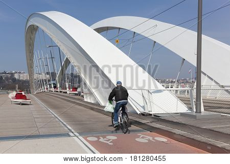 Lyon, France - March 15, 2017: Tramway and cyclist on a bridge near Confluence in Lyon, France