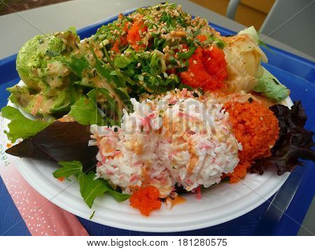 Hawaiian cuisine poki bowl with scoops of crab,spicy tuna,salmon,roe, avocado,pickled ginger and lettuce