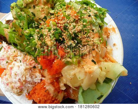 Hawaiian poki bowl with crab,ginger,avocado,and lettuce on plate