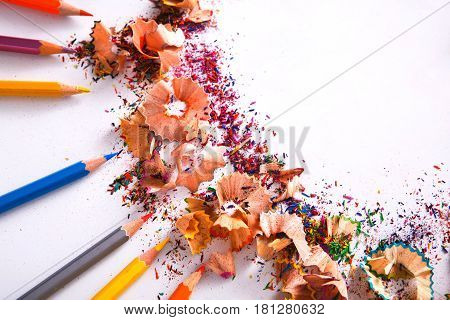 Drawing tools background. Lot of colorful pencils frame with sawdust and shavings on white, copy space, flat lay