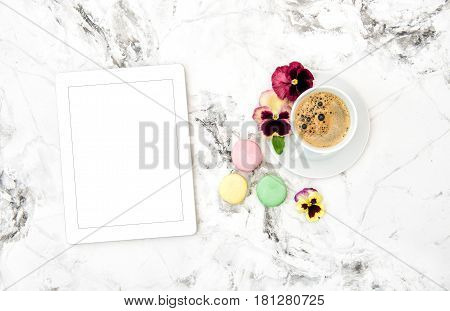 Tablet PC coffee french cookies macaroons spring pansy flowers. Floral flat lay. Minimal concept