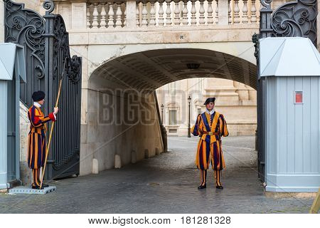 VATICAN - MAY 12, 2014: Famous Swiss Guard guarding the entrance to the Vatican City. The Papal Guard with about 100 men is the world's smallest army.