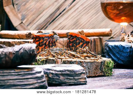 Details of smoke shop showcase in western style. Twist tobacco ropes on rustic cutting board. Various smoking pipes, tobacco, cigars and smokers alcohol on natural wood counter