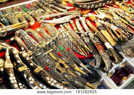 ISTANBUL - MAY 27, 2013: East edged weapons sold in the Grand Bazaar in Istanbul, Turkey. The Grand Bazaar is the oldest and the largest covered market in the world with 61 covered streets.