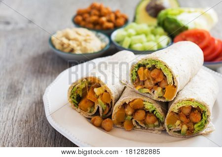 Delicious vegetarian wraps made with cajun chickpeas butternut squash spring onion cucumber avocado with ingredients on the back on the dark wooden table copy space for text